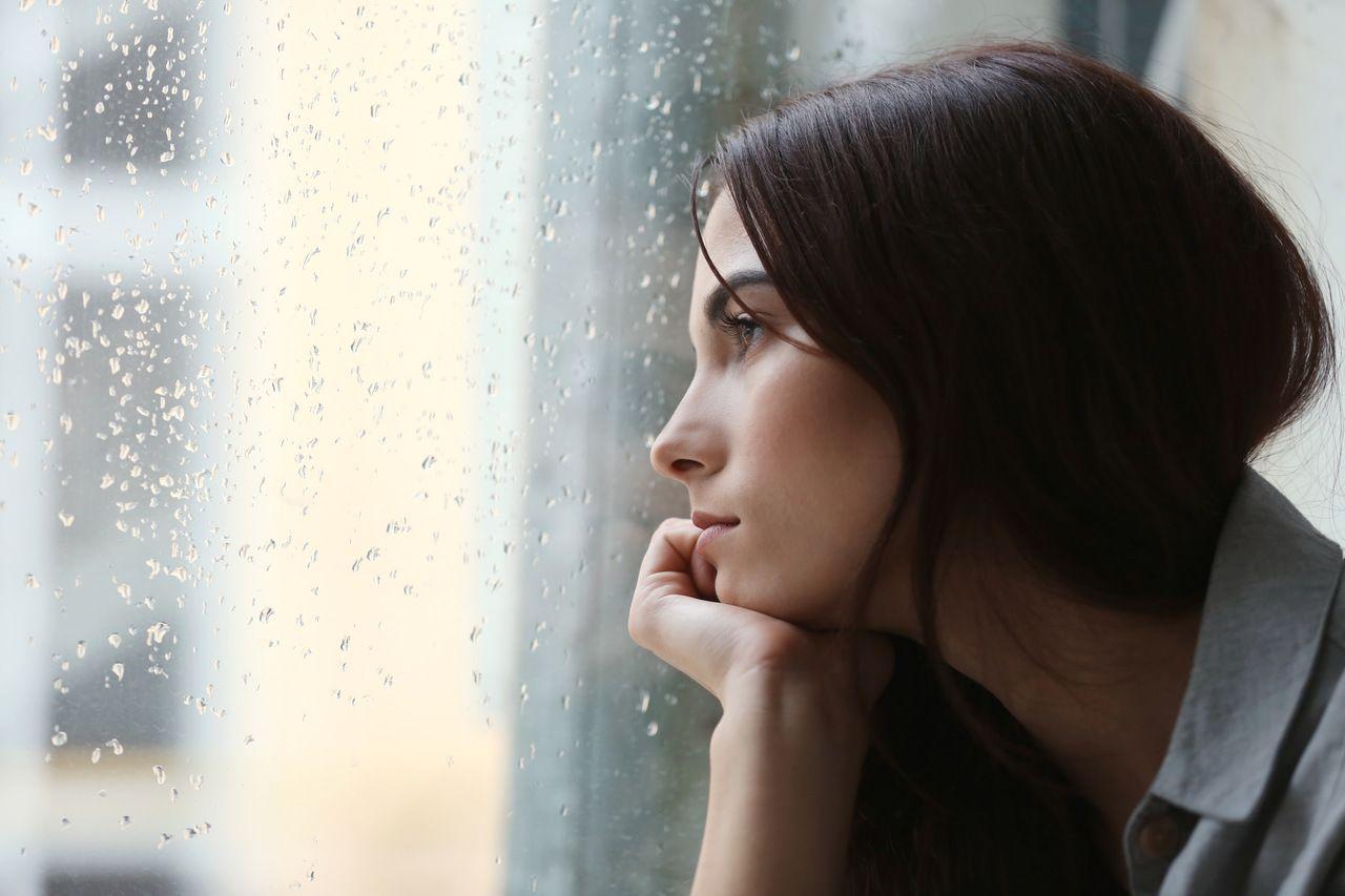 Zimowa depresja - smutna, przygnębiona młoda kobieta wpatrująca się w okno.